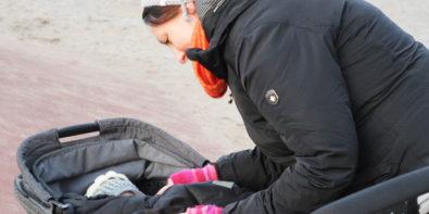 Familie unterwegs im Winter mit Kinderwagen
